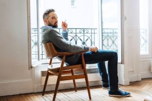 bearded man sitting by the window and smoke cigarettes